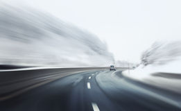 Fast danger driving. Danger and fast drive at the icy snow highway. Motion blur visualizies the speed and dynamics Royalty Free Stock Image