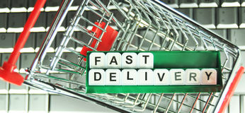 Fast delivery. Concept with shopping cart and laptop keyboard Royalty Free Stock Photos