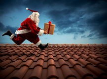 Fast delivery Santa Claus. Santa Claus runs with a big present on a house roof Stock Photo