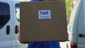 Fast delivery service courier in uniform holding cardboard box, express shipping. Stock footage stock video footage