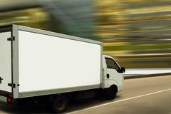 Fast delivery van on blurred background. White fast delivery white van on a modern street with a golden blurred background. The van is white and blank for your Stock Photography