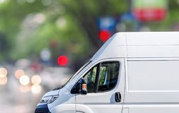 Fast delivery, van on city street blured bokeh background. Close Royalty Free Stock Images