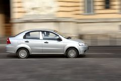 Fast driving. Silver car going at high speed in the street with panning effect Stock Image