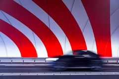 Fast driving black car in tunnel with stripes Stock Image