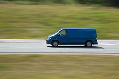 Fast driving blue minivan car royalty free stock photo
