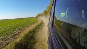 Fast driving a car in the countryside. The camera is outside and aimed back. stock footage