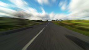 Fast driving car on the road in green fields stock video footage