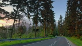 Fast driving a car on the road between the mountains in the Tatras at sunrise stock footage