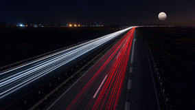 Fast driving on highway at night of full moon Stock Photos