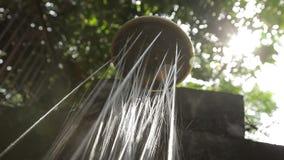Fast duschdysa med sprejer av varmt vatten utomhus i något exotiskt land stock video