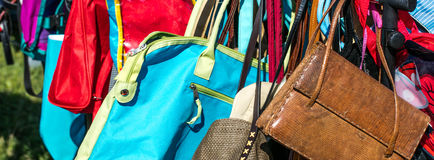 Fast fashion bags on display at thrift store to resale. Fast fashion women bags and purses on display at flea market or thrift store to resale, reuse, recycle royalty free stock image