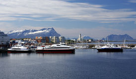 Fast ferries in harbour of Bodo, Norway. With snowy mountains on the background Stock Photo