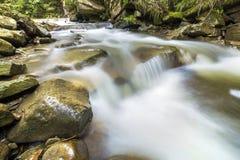 Fast flödande flodström med slätt silkeslent vatten som faller från stora stenar i härliga vattenfall på ljus solig sommardag arkivfoton