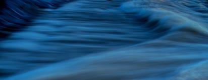 Fast flödande vatten i lång exponering för bakgrunds- och räkningsfotoet - blått Arkivbild