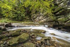 Fast fl?dande flodstr?m med sl?tt silkeslent vatten som faller fr?n stora stenar i h?rliga vattenfall p? ljus solig sommardag arkivbilder