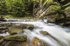 Fast fl?dande flodstr?m med sl?tt silkeslent vatten som faller fr?n stora stenar i h?rliga vattenfall p? ljus solig sommardag royaltyfri fotografi