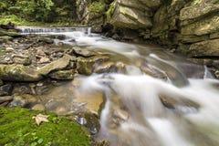 Fast fl?dande flodstr?m med sl?tt silkeslent vatten som faller fr?n stora stenar i h?rliga vattenfall p? ljus solig sommardag royaltyfria foton