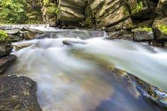 Fast fl?dande flodstr?m med sl?tt silkeslent vatten som faller fr?n stora stenar i h?rliga vattenfall p? ljus solig sommardag arkivfoton