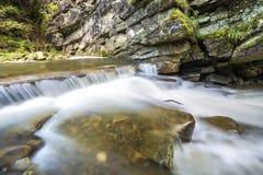 Fast fl?dande flodstr?m med sl?tt silkeslent vatten som faller fr?n stora stenar i h?rliga vattenfall p? ljus solig sommardag arkivbild