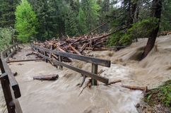 Fast flooding and logs and debris against pedestrian bridge royalty free stock photography
