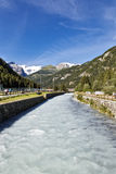 Fast flowing river and snowy alpine peaks. In Champoluc in norther Italy with people walking alongside the river towards distant buildings nestling in the Stock Photos