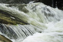 Fast flowing water over rocks Stock Photos
