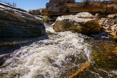 Fast flowing water in Sabino Creek. Water quickly flows past the rocks in Sabino Creek in Tucson, Arizona Royalty Free Stock Photos