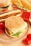 Fast food. Couple hotdog, hamburger and ingredients. Fast food composition Stock Photography