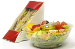 Fast-food. A close up view of a bowl of salad and a box with sandwiches Royalty Free Stock Image