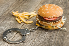 Fast food addicted. Handcuffs and hamburger on wooden background. Part of project Addicted royalty free stock photo