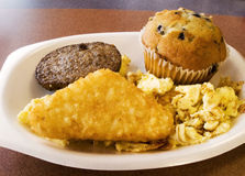 Fast Food Breakfast. Sausage, scrambled eggs, potatoes, and blueberry muffin breakfast from a fast food restaurant Royalty Free Stock Photo