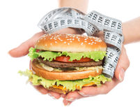 Fast food burger cheeseburger in hands with measure tape Stock Photography