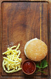 Fast food burger with french fries. On a wooden board Royalty Free Stock Photo