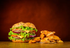 Fast Food Burger and Fried Potatoes. Fast Food with Big Burger with crunchy Fried Potatoes Royalty Free Stock Photography