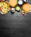 Fast food. Burgers with fries and cola. On the black chalkboard Stock Images