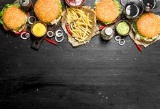 Fast food. Burgers with fries and cola. On the black chalkboard Royalty Free Stock Photos