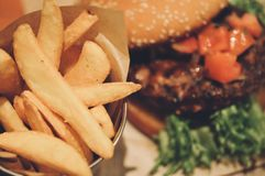 Fast food concept. Female hand taking french fries near big fresh burger. royalty free stock photo