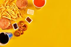 Fast food concept with greasy fried restaurant take out as onion rings, burger, fried chicken and french fries as a Royalty Free Stock Image