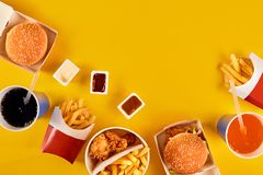 Fast food concept with greasy fried restaurant take out as onion rings, burger, fried chicken and french fries as a