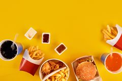 Fast food concept with greasy fried restaurant take out as onion rings, burger, fried chicken and french fries as a Stock Photo