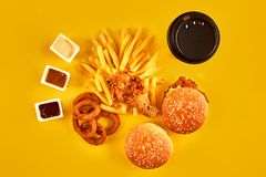 Fast food concept with greasy fried restaurant take out as onion rings, burger, fried chicken and french fries as a Royalty Free Stock Photography