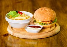 Fast food concept. High calorie snack. Burger menu. Hamburger with sesame seeds and french fries and tomato sauce on royalty free stock images