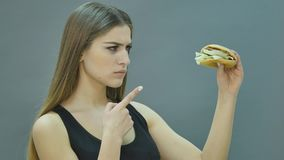 Fast food concept. Tasty unhealthy burger sandwich hamburger in hands hungry mouth getting ready to eat isolated on a stock footage