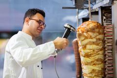Chef slicing doner meat from spit at kebab shop Stock Images