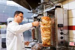 Chef slicing doner meat from spit at kebab shop Stock Photography