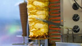 Meat grilling on rotating spit at kebab shop. Fast food and cooking concept - meat grilling on rotating spit at kebab shop stock video