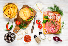 Fast Food and Cooking Ingredients. Fast Food Burger, Cold Cola and French Fries with Raw Ground Beef and Bacon and Cooking Ingredients Royalty Free Stock Photography
