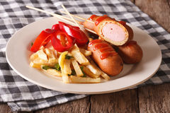 Fast food: corn dog and fries on a plate close-up. horizontal Royalty Free Stock Photos