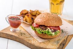 Fast food dish. Appetizing meat burger, potato chips and sauce. Takeaway composition. Royalty Free Stock Image