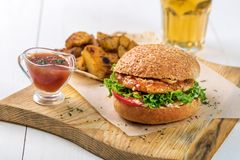 Fast food dish. Appetizing meat burger, potato chips and sauce. Takeaway composition. Stock Photography